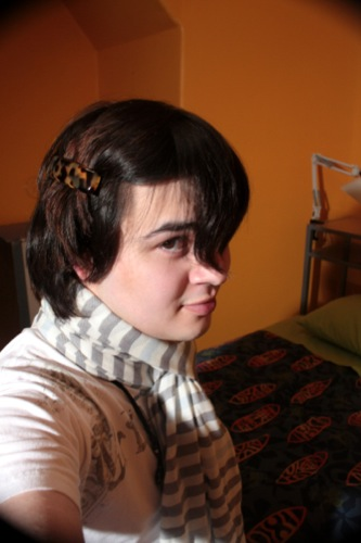 Person with medium length brown hair pulled back in a hairclip on one side, wearing a white shirt and a grey-and-white striped scarf.