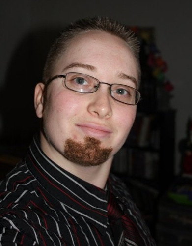 A man with a neatly maintained goatee beard, wearing a striped shirt and glasses.