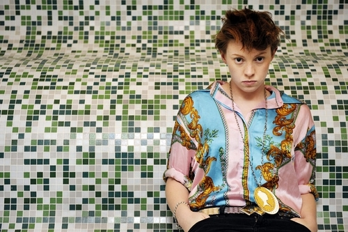 Elly Jackson, a pale person with short hair gelled to swoop over their forehead, wearing a brightly patterned shirt and a pendant necklace, staring at the camera while sitting against a curved mosaic-style tile wall.