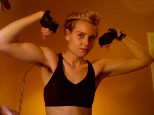 A person with short hair, wearing fingerless gloves and a black chest covering of some sort, flexing their rather impressive muscles.