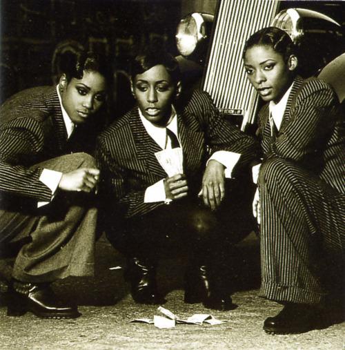 3 women of color in pinstipe suits