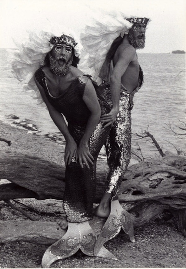 "Grayscale photo of two people with beards and long hair, dressed up as mermaids, with sequined ""tails"" and glittery makeup all over their faces."