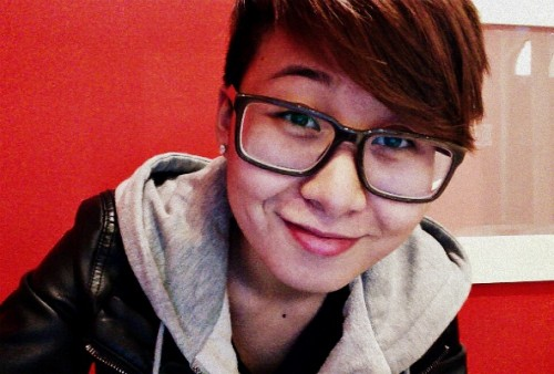 Smiling person with large glasses and short hair with longish bangs, wearing a grey hoodie and a leather jacket.
