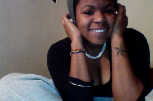 A smiling person with facial piercing and a tattoo of a star on their forearm, wearing a white necklace, a rainbow wristband, and a black low-cut shirt.