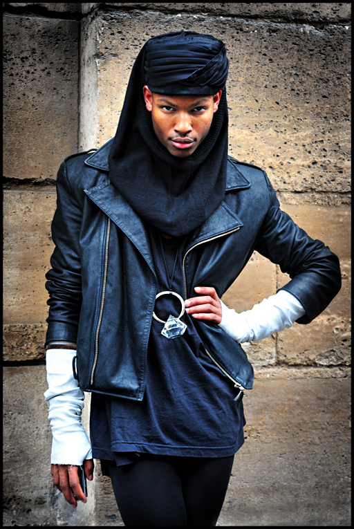 Photo of Jean Paul Paula in an androgynous outfit featuring a headscarf, a blck leather jacket, and an oversized diamond ring as a necklace pendant.