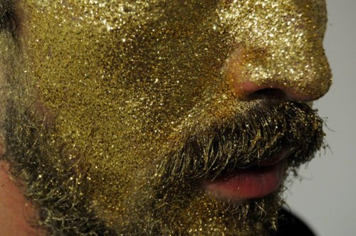 lower half of face, covered in gold glitter, with beard