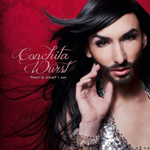 Cover photo: Conchita Wurst: That's What I Am. -- A person with long, black hair, and full black beard, in a dress/top full of silver sequins. They are in front of a silky deep red background, and they have one hand slightly raised.