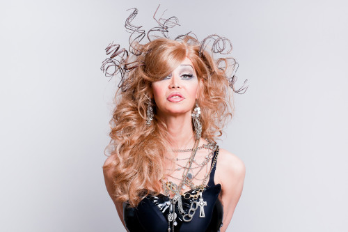 Portrait of Nina Arsenault, with long wavy dark blonde hair, some strands randomly curling and defying gravity, wearing a shiny black shoulder-free top, and lots and lots of necklaces.