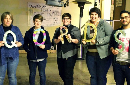 "Five people holding up the letters ""Q"", ""O"", ""R"", ""D"", ""S""."
