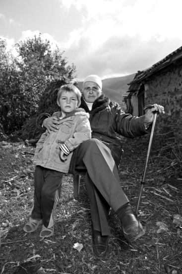 Hajdari, a sworn virgin: a person with their hair covered, sitting outside, clasping a walking stick in one hand and a young child in the other.