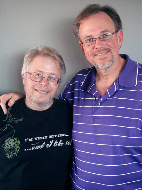 "A couple with their arms around each other, smiling openly into the camera. Both wear glasses and have grey beards. The shirt of the shorter one says ""I'm very bitter... and I like it!""."