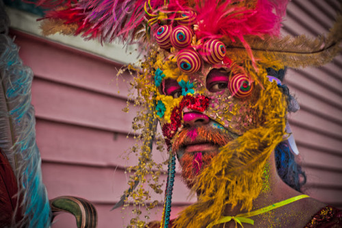 Portrait shot of a person with a short beard painted orange with a hot-pink strip down from the nose, wearing a carnivalesque mask with glitter, beads, and lots of feathers. The colours are mostly yellow and hot-pink with some cyan.