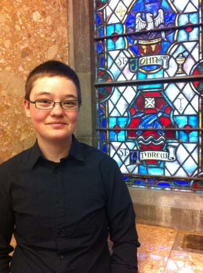 A person with very short brown hair and glasses next to a church's stained-glass window.